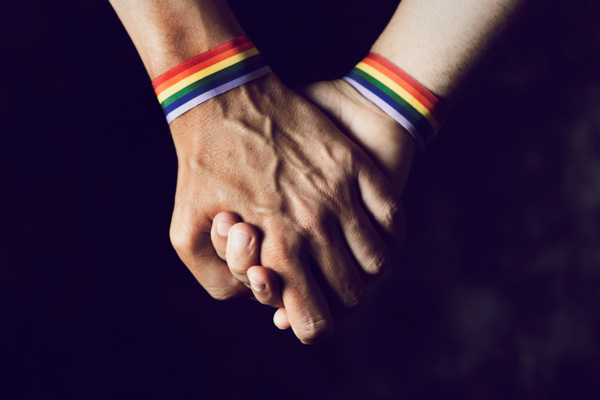 holding hands with rainbow bracelets